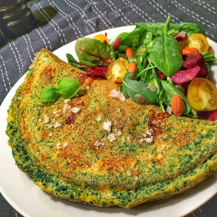 Saftig spinatomelet med sprød bladsalat, tomat, mandler og græskarkerner